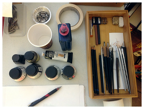 Tools of the trade, all laid out and ready for action:  ink, nibs, brushes, and a brave, solitary pencil.